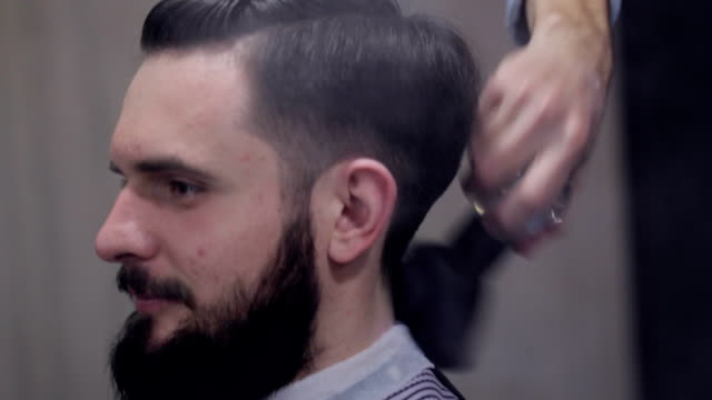 Male barber make a haircut for bearded client and using a talc at barbershop video