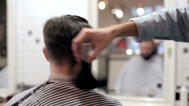 Male barber with a male client at barbershop. Barber using a talc. video