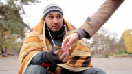 Male beggar sitting in public place with sad face, kind woman giving him charity video
