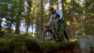 SLO MO Male biker riding a bumpy forest trail video
