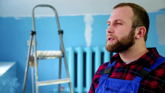 male Builder smokes cigarettes in the repair room video