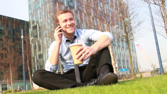 Male Business executive working outside in park video