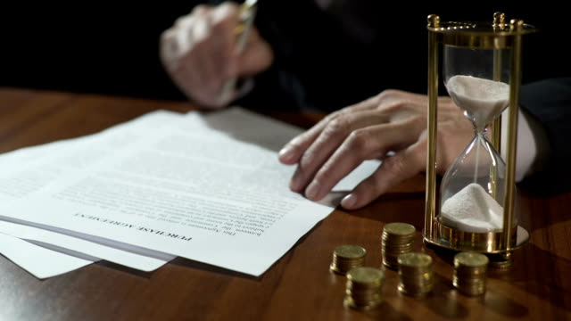 Male buyer or seller signing purchase agreement, money and hourglass on table video