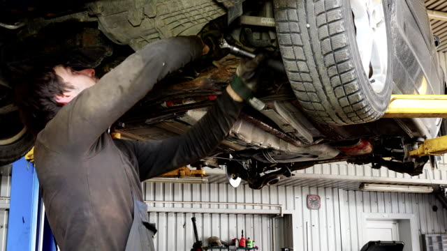 Male car mechanic with spanner working under automobile in garage video