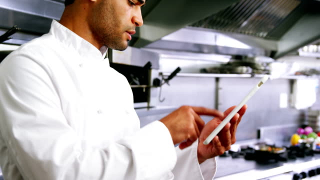 Male chef using digital tablet in commercial kitchen video