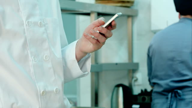 Male chef's hands holding mobile phone in the restaurant kitchen video