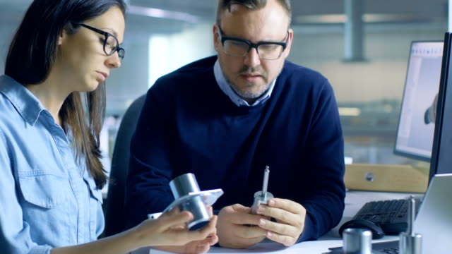 Male Chief Engineer Consults with Female Technician about Component Durability. Computer Display Shows 3D Designed Turbine/ Engine Part. video