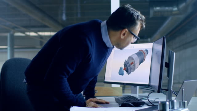 Male Chief Engineer Sits at His Working Place with Turned on Personal Computer starts Designing 3D Turbine/ Engine Model with Help of Cad Software. video