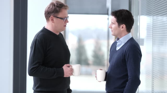 DS Male colleagues talking over cup of coffee in hallway video