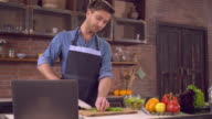 Male cook romantic lunch using internet indoors video
