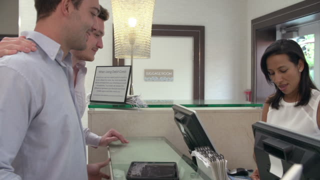 Male Couple Check In At Hotel Reception Using Digital Tablet video