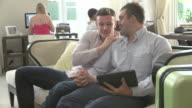 Male Couple Sitting In Hotel Lobby Looking At Digital Tablet video