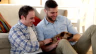 Male couple talking and petting their dog video