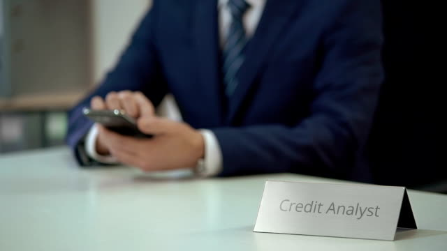 Male credit analyst working in mobile application, reading financial market news video