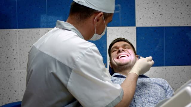 Male dentist examining teeth of his male client video