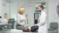 Male Doctor Consults His Mid Adult Female Patient. Nurse Busily Works at the Computer in the Background. video