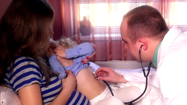 male doctor examining sick girl child with stethoscope sitting on mother knees video