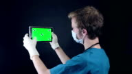 Male doctor holding, showing digital tablet with green screen video