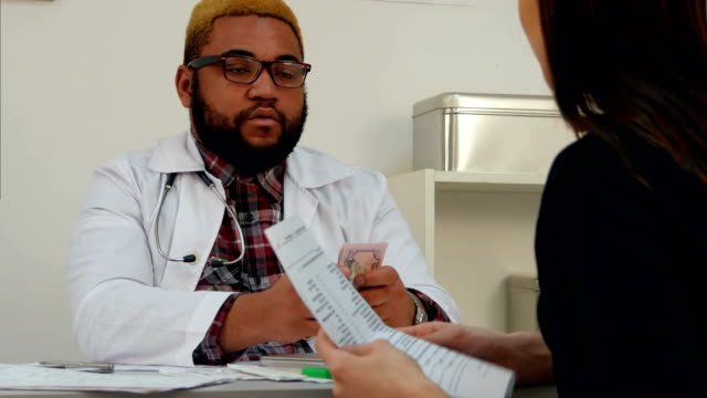 Male doctor putting money in his pocket paid by female patient for medical visit video