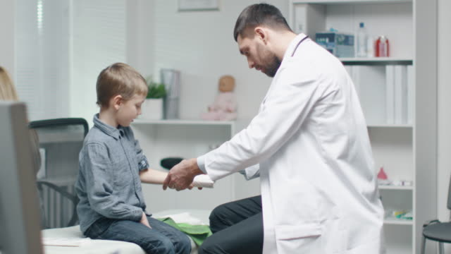 Male Doctor Removes Plaster from a Boy's Healed Hand. Boy is Very Happy. They Do High Five. In Slow Motion. video