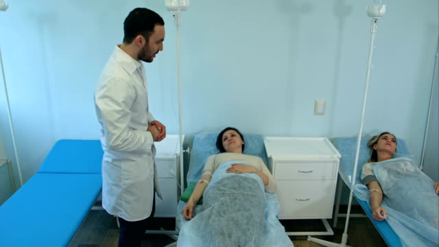 Male doctor talking to female patients on drip resting in hospital ward video