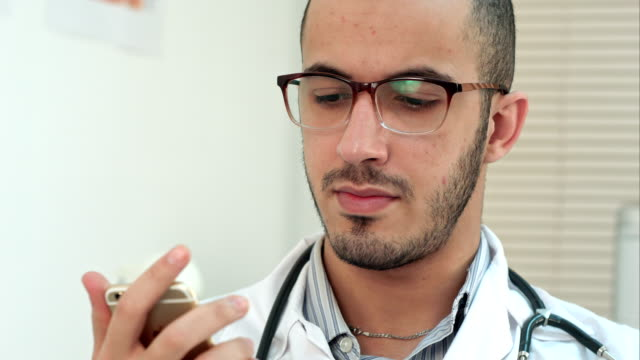 Male doctor texting on a smartphone video