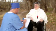 Male doctor with recovering senior patient in wheelchair video
