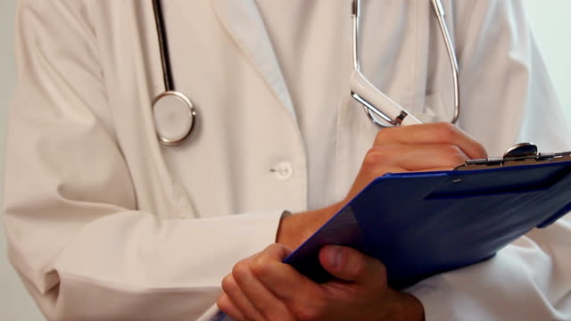 Male doctor writing Rx prescription on clipboard, taking notes video