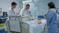 DS Male doctors visiting patient on round through ICU video