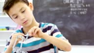 Male elementary STEM student uses tool to build robot at school video