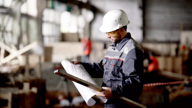 Male engineer in protective hardhat standing in the building site holding construction plan and spirit level. Inspector checking process of construction and expressing his disapproval with results video