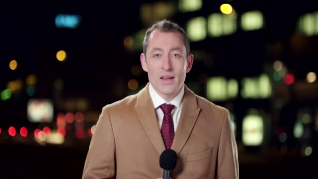Male English reporter reporting live from the city at night video