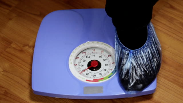 Male feet in shoe covers stepping on blue scales at hospital, close-up video