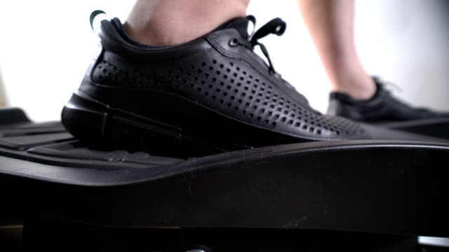 Male feet in sneakers on foot pedals of cross trainer during workout video