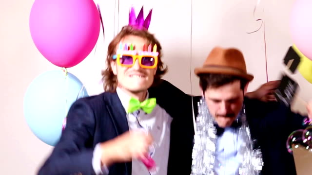 Male friends dancing with a sign in love in photo booth video