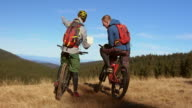 Male friends on bikes discussing the right trail on map video
