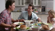Male gay couple and daughter dining in their kitchen, shot on R3D video