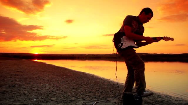 Male guitarist playing rock and jump at sunset video