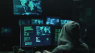Male hacker in a hood works on a computer with maps and data on display screens in a dark office room. video