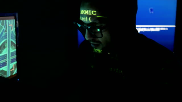 Male hacker working on computer while green code characters reflect on his face in a dark office room, IT professional programmer in glasses is working video