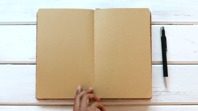 A male hand close diary book  on the white wooden desk, top view and overhead shot use for blank template book mock up to add any text content video