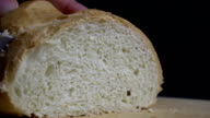 Male hand cutting loaf of bread. video