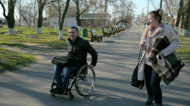 male handicapped and girl walk along embankment, cripple person video