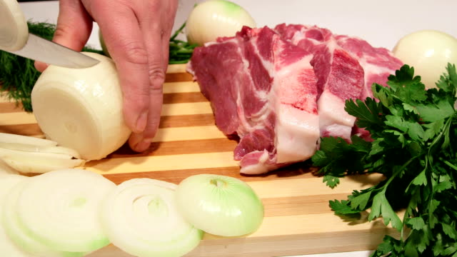 Male hands chopping onion for pork meat cooking video