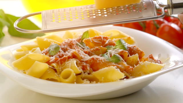 Male hands grating cheese over penne pasta video