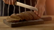 Male hands slicing home-made bread on wooden table video