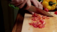 Male hands slicing tomato on wooden board, tracking shot video