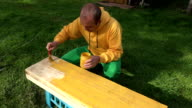 Male handyman with brush and paint jar in hands painting wooden plank board surface in yellow. FullHD video