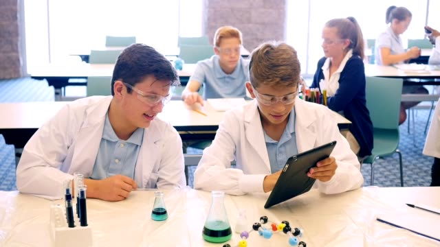 Male high school STEM students prepare for chemistry experiment video