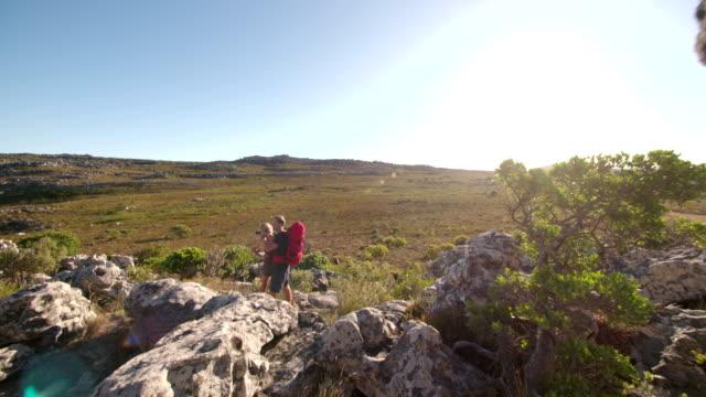 Male Hiker looking through binoculars while hiking woman is pointing video